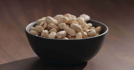 Roasted salted pistachios in black bowl on walnut table Zdjęcie Seryjne