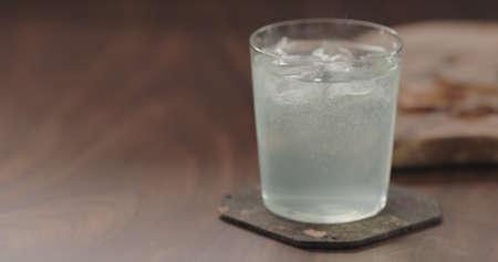 green sparkling drink in tumbler glass from walnut table Zdjęcie Seryjne
