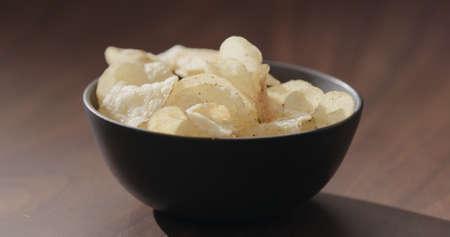 potato chips in black bowl on walnut table