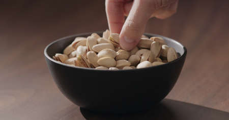 Man hand take roasted salted pistachios from black bowl on walnut table