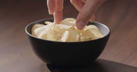 man hand take potato chips from black bowl on walnut table Zdjęcie Seryjne