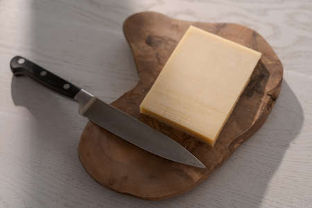 Small block of aged cheese on wood board with knife Zdjęcie Seryjne