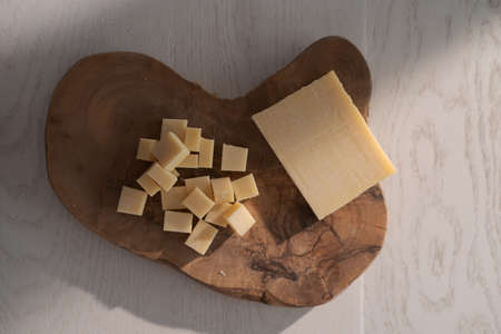 Small block of aged cheese sliced in small pieces on wood board Zdjęcie Seryjne