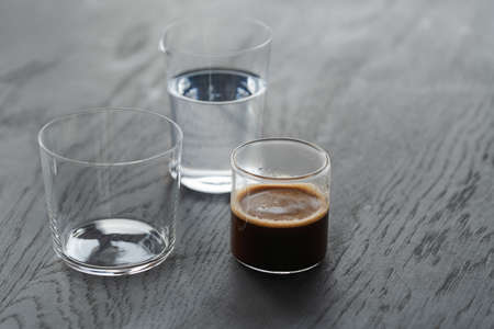 Ingredients for espresso tonic with clear ice cube in tumbler glass on oak wood table with copy space Zdjęcie Seryjne