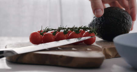 man put cherry tomatoes on a branch and avocado on wood table Zdjęcie Seryjne