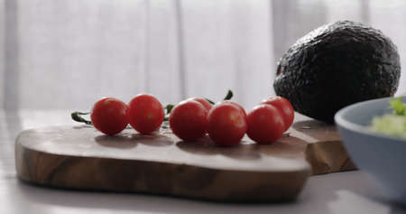 cherry tomatoes and avocado on wood table