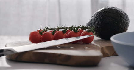 cherry tomatoes on a branch and avocado on wood table