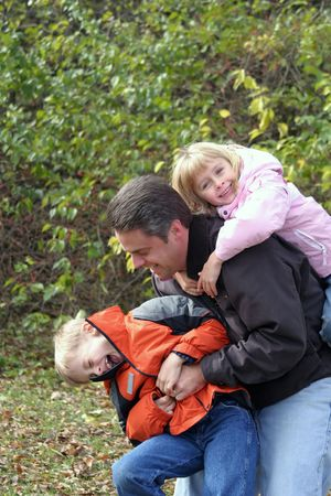 Father playing with son and daughter outside