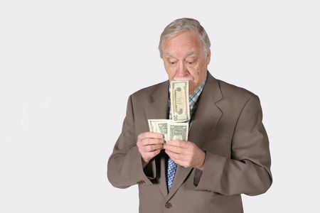 Mature senior man counting money holding bill in his mouth Stock Photo - 650594