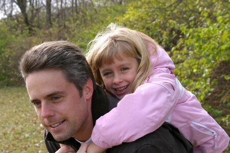 blonde girl and father smiling and having fun outside