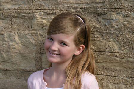 preteen mooie blonde meisje in het roze lachend buitenshuis door stenen muur Stockfoto