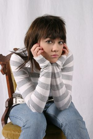 sad brunette teen girl with green eyes seated with head in hands