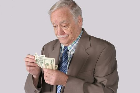 senior mature man in business suit counting money