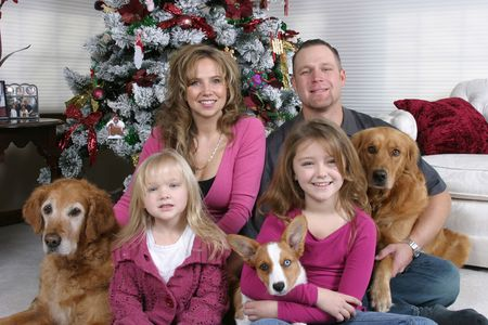 christmas house: smiling family and dogs sitting by Christmas tree