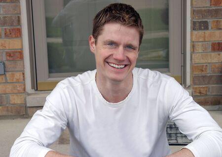 Sourire heureux beau mec assis dehors sur la véranda  Banque d'images - 650579