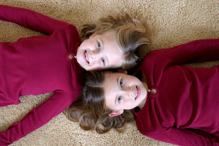 smiling young girls in red shirts laying on tan carpet