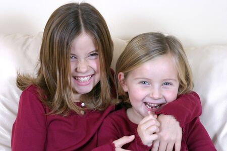 young girls in red shirts laughing and smiling Stock Photo