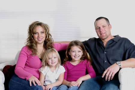 mother, father and daughters sitting on couch smiling Stock Photo