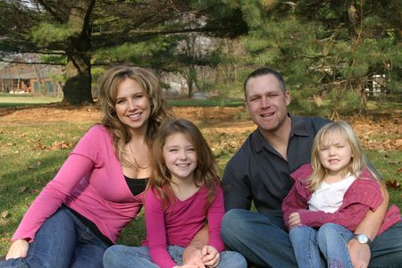 mother, father and daughters outside sitting on ground in forest Stock Photo - 650566