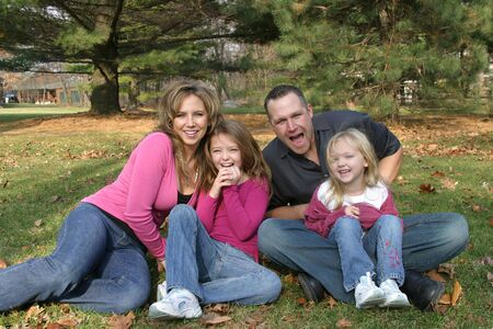 mother,father and daughters sitting in forest laughing