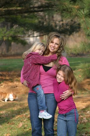 mother and daughters smiling and happy in forest photo