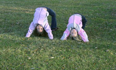 giovani ragazze ouside in autunno facendo backbends in erba