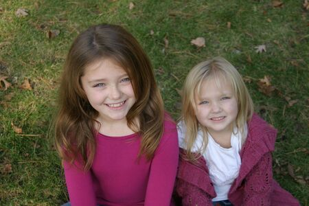 beautiful little girls sitting in grass looking up into the camera