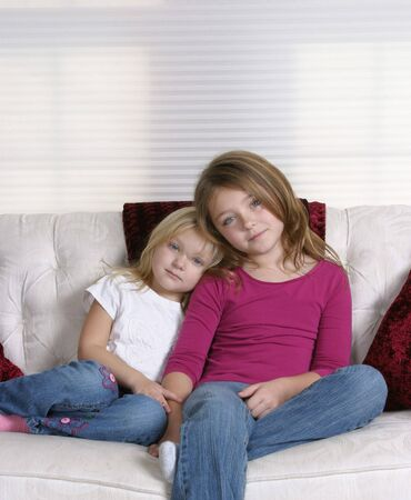 pretty blonde and brunette young girls sitting on white couch