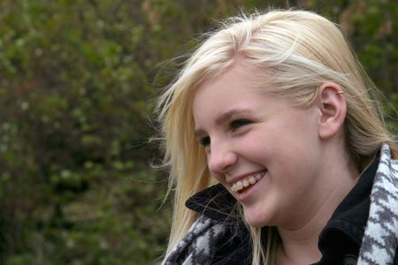 pretty blonde girl with braces smiling outside