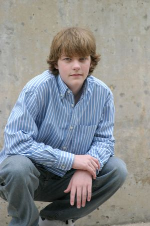 brown haired young teen boy crouching by cement wall Stock Photo - 3054952