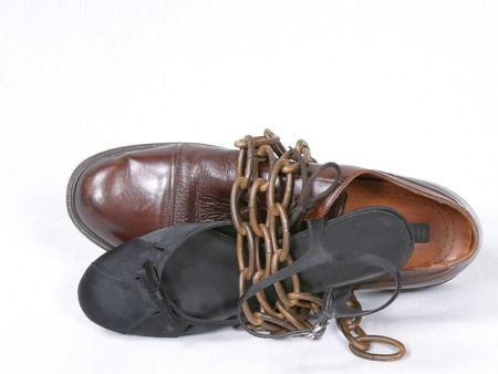 chainlinks: man and woman dress shoes bound together with bronze chain Stock Photo