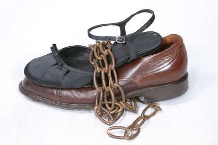 man and woman dress shoes tied together by chain photo