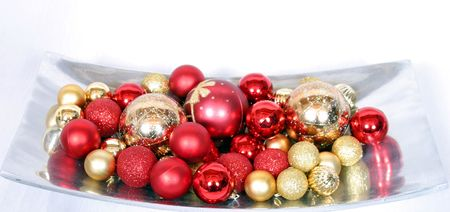 red and gold christmas tree ornaments in silver tray on white