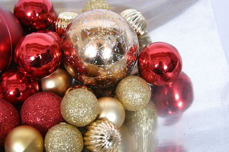 red and gold shiny christmas tree ornaments on silver tray