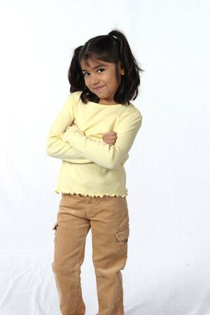 cute little girl with dark hair and eyes with crossed arms