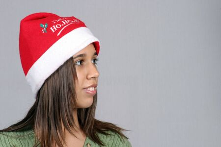 Beautiful latina girl in Santa hat looking to her left photo