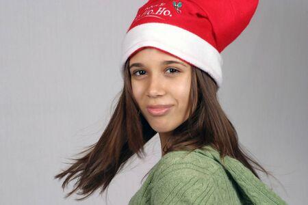 pretty hispanic girl smiling and twirling in santa hat photo