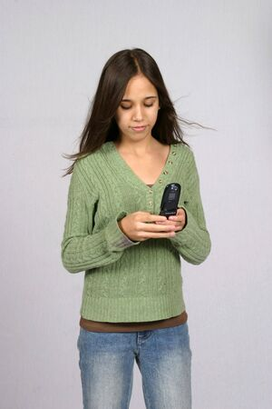 preteen girl: pretty dark hair preteen girl texting on her cell phone Stock Photo