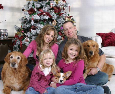 smiling family and dogs sitting by Christmas tree