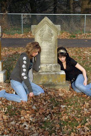 sad teenage girls sitting by gravestone in cemetary Stock Photo - 688232