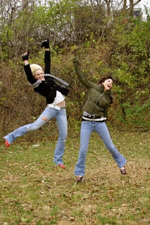 blonde and brunette teen girls outside in autumn jumping Stock Photo