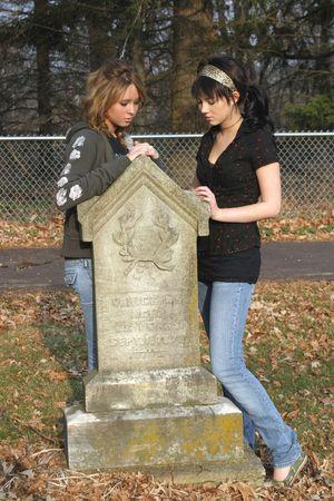 sitting on the ground: sad teenage girls sitting by gravestone in cemetary Stock Photo