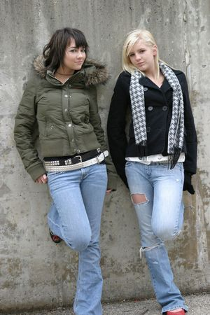 Blonde and brunette teenage girls standing in alley in jeans