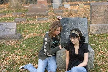 sad blonde and brunette teen girls sitting in graveyard photo