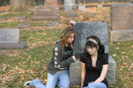sad teenage girls sitting by gravestone in cemetary photo