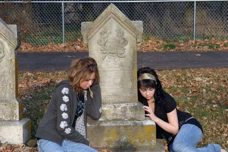 sad teenage girls sitting by gravestone in cemetary Stock Photo - 688224