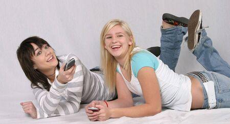 Brune et souriante blonde adolescentes portant sur parole à regarder la télévision  Banque d'images - 688098