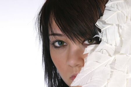 pretty brunette peeking out from white feathers photo