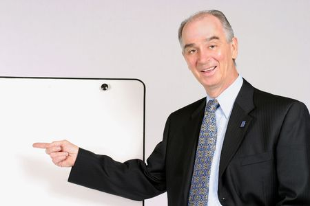 Caucasian business man pointing to white board