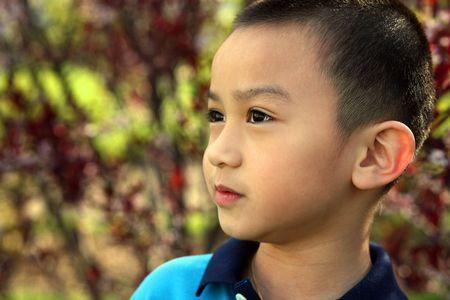 closeup of adorable asian boy outside looking away